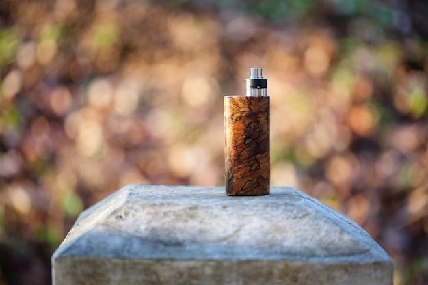 ボケテクスチャ背景に再構築可能な滴下アトマイザーと自然の安定した木製ボックス改造 Premium写真