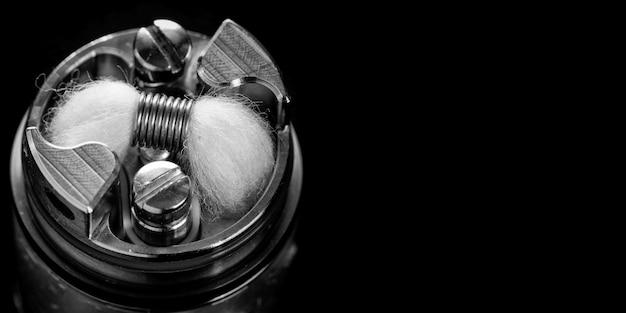 フレーバーチェイサー、ベイピングデバイス、ベイプギア、気化器機器用のハイエンドの再構築可能な滴下タンクアトマイザーに、日本製オーガニックコットン芯を備えた白黒のシングルマイクロコイル Premium写真