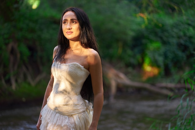 顔に夕方日光で濡れた毛で川の近くに屋外白いウェディングドレスの若いかなりブルネットの女性 Premium写真