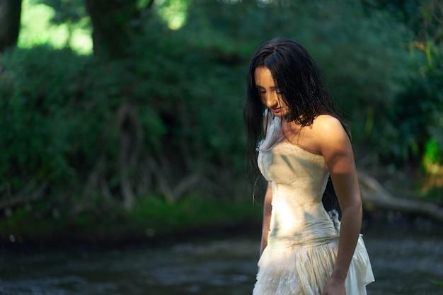 濡れた毛で川の近くに屋外白いウェディングドレスの若いかなりブルネットの女性 Premium写真