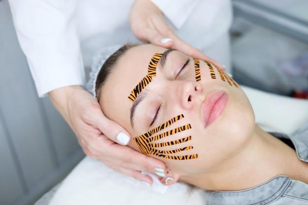 美容院で虎色のテープを使用してテーピング顔手順を作る美容師 Premium写真