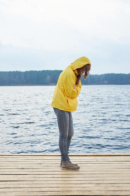 湖の桟橋の上に立って、暖かくしようとして自分を抱いて黄色いレインコートを着た赤毛の女性。曇った厄介な秋の天気。 Premium写真
