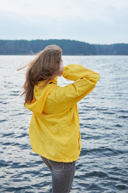 湖の近くに座り、遠くを見て黄色のレインコートの赤毛の女性。曇った厄介な秋の天気。 Premium写真