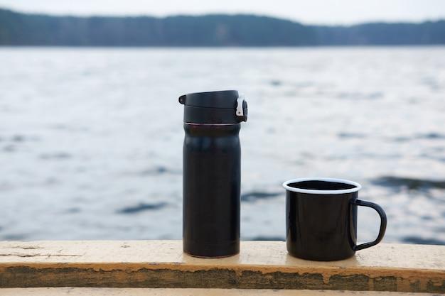 魔法瓶、湖の上のコーヒーの黒いマグカップ、 Premium写真