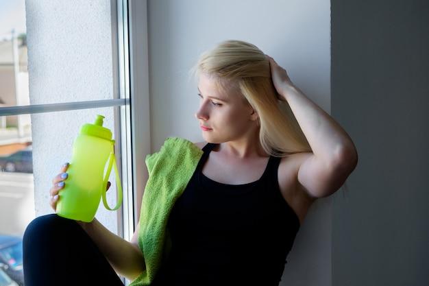 Молодая женщина пьет воду в тренажерном зале Premium Фотографии