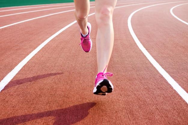 Спортивная молодая женщина в розовых кроссовках бегает по стадиону беговой дорожки Premium Фотографии
