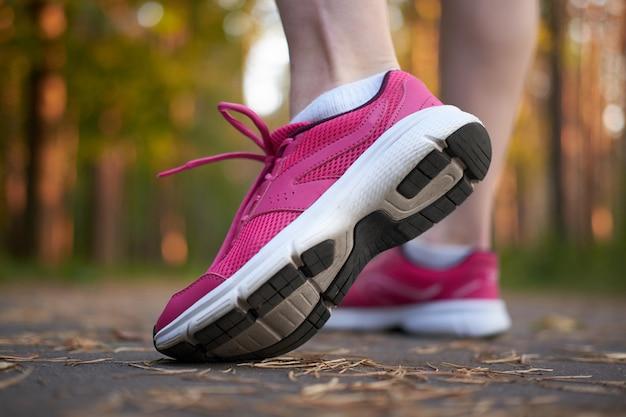 Спорт. женские ножки в розовых кроссовках на пробный запуск в лесу. крупный план на спортивной обуви бегущей женщины. бегать Premium Фотографии