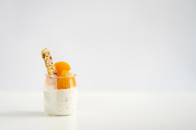 Баночка йогурта или творога с мюсли и консервированными абрикосами Premium Фотографии