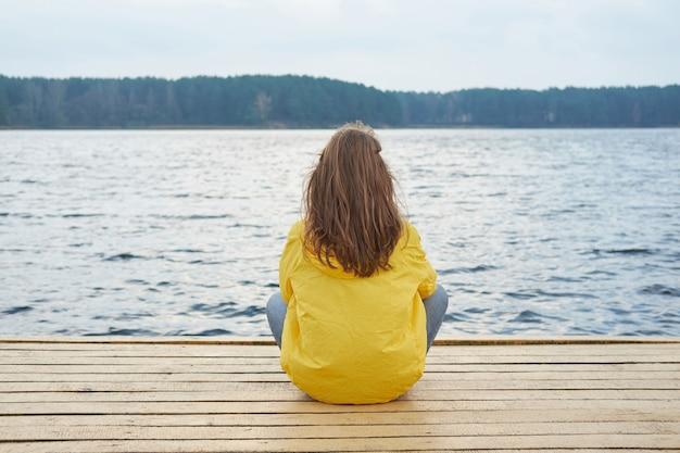 湖の桟橋に座っている黄色のレインコートで赤毛の女性 Premium写真