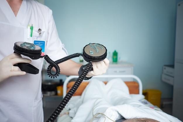 医師の集中治療医が重要な患者の除細動を行います Premium写真