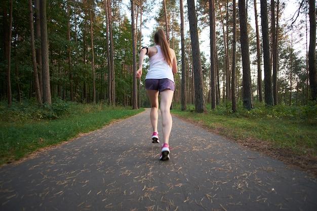 Рыжая молодая тощая женщина работает в лесу летом. бег по утрам. Premium Фотографии