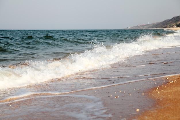 Бурное море фон. волны и брызги. песчаный пляж. Premium Фотографии