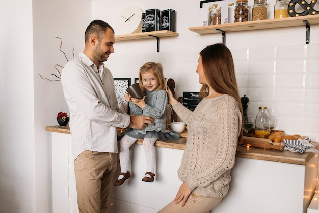 Жизнерадостные родители и их милая девушка дочери в кухне дома. Premium Фотографии