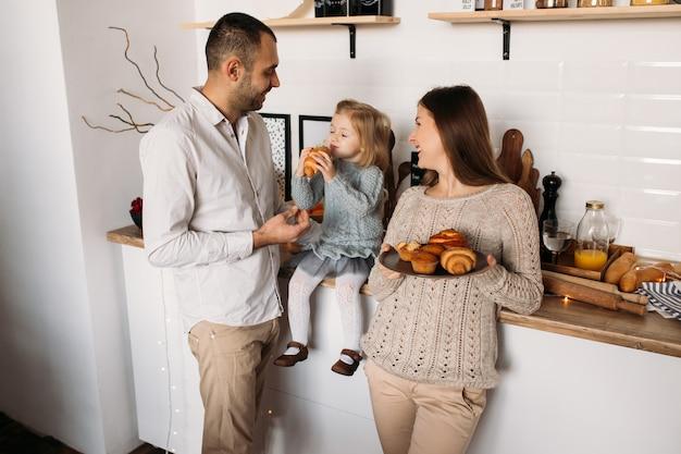 クロワッサンを食べる母と娘。台所で幸せな家族 Premium写真