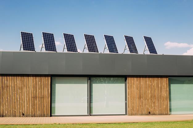 屋根にソーラーパネルが付いたモダンな家。グリーン電力、再生可能な代替エネルギー Premium写真