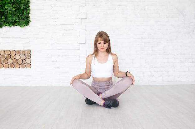 ヨガをやっている床に座っている若い女性 Premium写真