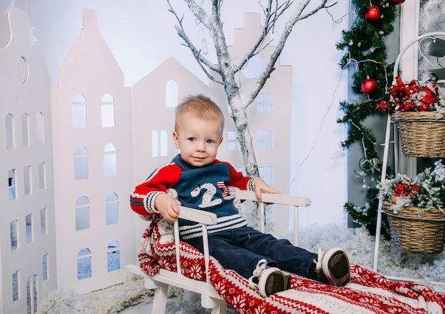 冬のインテリアで、木製の装飾されたそりに座っている小さな男の子。メリークリスマスと新年の概念 Premium写真