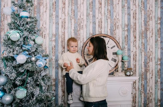 母とクリスマスツリーの近くの小さな男の子。クリスマス、新年、冬、休日の季節の概念。家族。 Premium写真