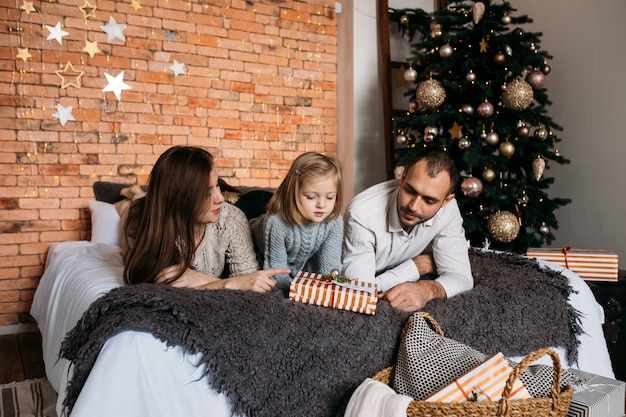 Счастливого рождества и счастливых праздников! жизнерадостные родители и их милая дочь обменивают подарки на кровати дома. Premium Фотографии