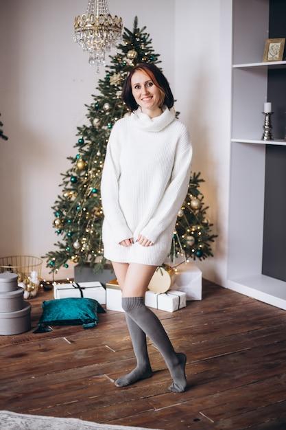 自宅のクリスマスツリーの近くの女性の笑みを浮かべてください。 Premium写真