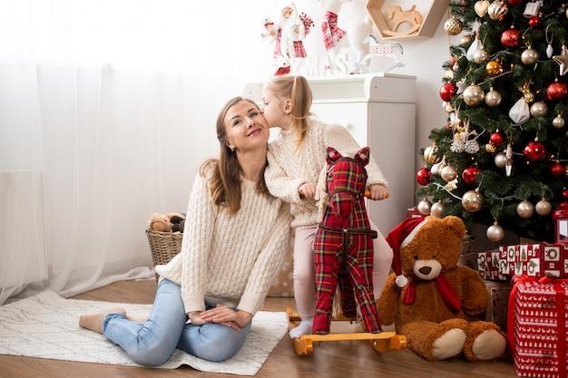 クリスマスツリーとギフトボックスの近くに自宅で母親にキスの女の子 Premium写真