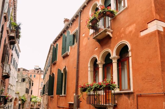 Окна и балконы с цветами в венеции, италия. Premium Фотографии