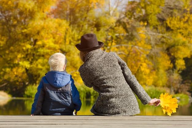 金髪の少年と彼の母親は、ドックに座って Premium写真