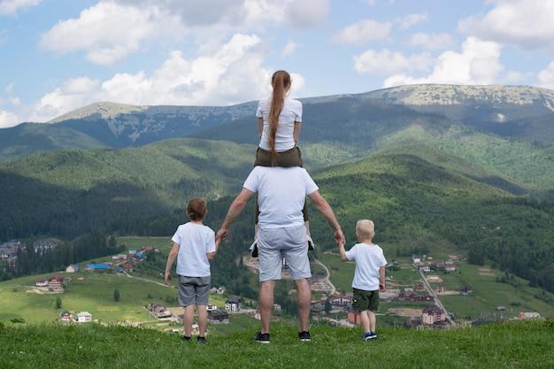 Семья с двумя сыновьями стоит на холме, глядя на горы. Premium Фотографии
