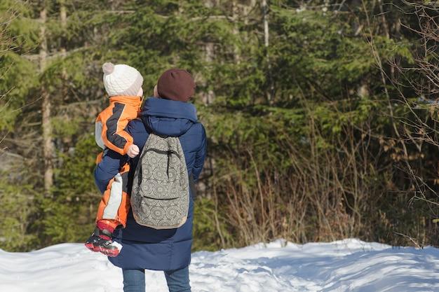 Мать с сыном на руках и рюкзаком стоит на фоне хвойного леса Premium Фотографии
