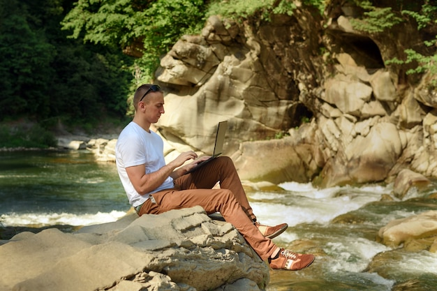 自然概念で動作します。滝と緑の木々の川の土手に座ってノートを持つ男。側面図 Premium写真