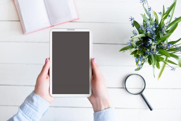 Женские руки с планшетом. черный пустой экран. стол с блокнотом и цветами Premium Фотографии