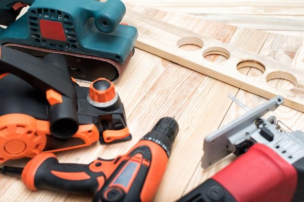 Набор ручных деревообрабатывающих электроинструментов для деревообработки и заготовки лежит на светлом деревянном. закрыть Premium Фотографии