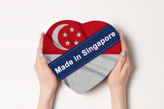 シンガポールの国旗をシンガポールで作った碑文。ハート型のボックスを保持している女性の手。 Premium写真