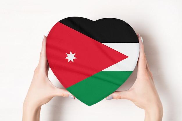 女性の手でハート型ボックスにヨルダンの旗 Premium写真