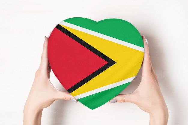 女性の手でハート型ボックスにガイアナの旗 Premium写真