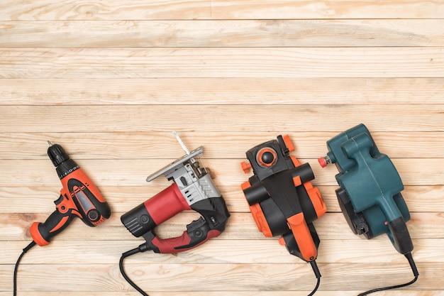 Набор ручных столярных электроинструментов для деревообработки лежит на светлом деревянном фоне. прямо выше Premium Фотографии