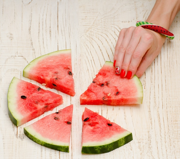 スイカと明るい木製のマニキュアで女性の手の三角形の部分 Premium写真