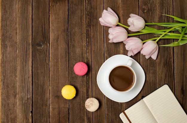 一杯のコーヒー、マカロン、ピンクのチューリップ、木製の背景上のノートブック。 Premium写真