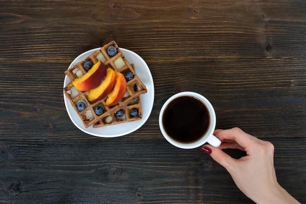 Бельгийские вафли с фруктами и ягодами. женская рука с чашкой кофе. вид сверху Premium Фотографии