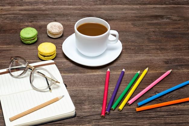 コーヒーマグ、マカロン、色鉛筆、ノート Premium写真