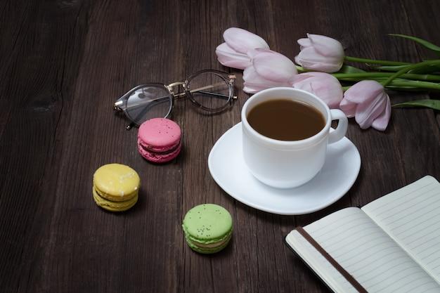 紅茶、マカロン、グラス、ピンクのチューリップ、ノート Premium写真