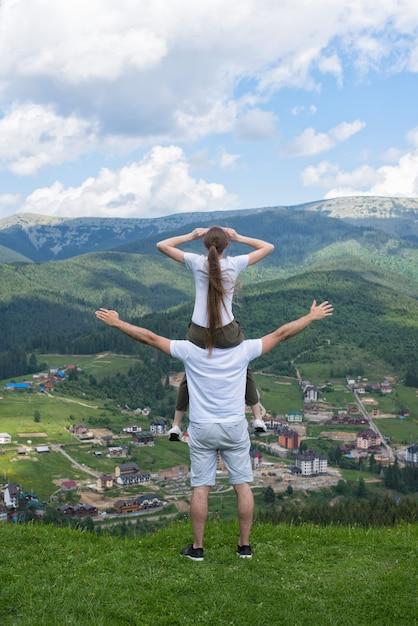 女の子は男の肩に座って、山を賞賛します。背面図 Premium写真