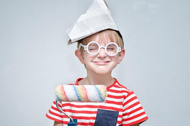 Забавный мальчик в бумажной шляпе с роликом в руках. Premium Фотографии