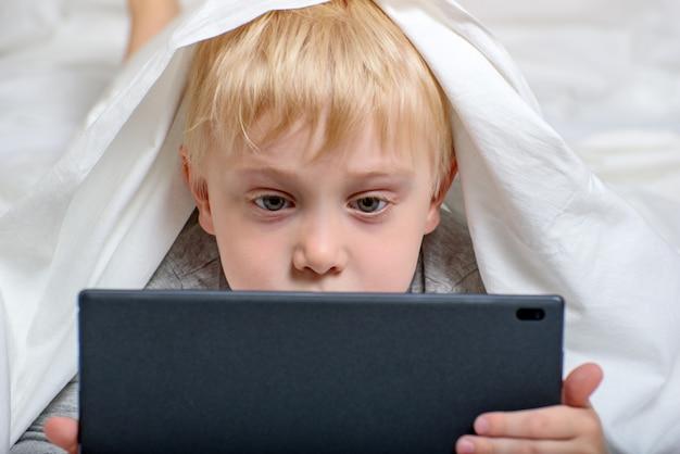 金髪の少年は、タブレットで何かを見ています。ベッドに横になり、カバーの下に隠れます。ガジェットレジャー Premium写真