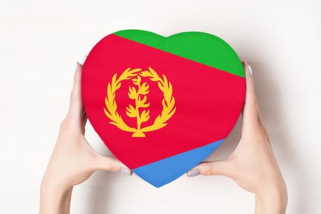 女性の手でハート形ボックスにエリトリアの旗。 Premium写真