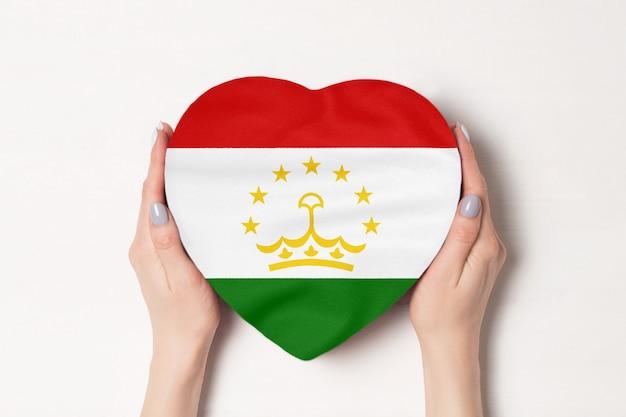 女性の手でハート型のボックスにタジキスタンの旗。 Premium写真