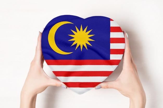 女性の手でハート形ボックスにマレーシアの旗。 Premium写真