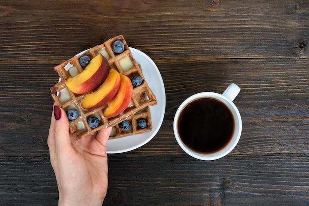 Женская рука с бельгийскими вафлями с фруктами и ягодами. чашка кофе. деревянный фон вид сверху Premium Фотографии