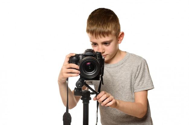 男子生徒はデジタル一眼レフカメラでビデオを撮影します。正面図。白い背景、分離 Premium写真