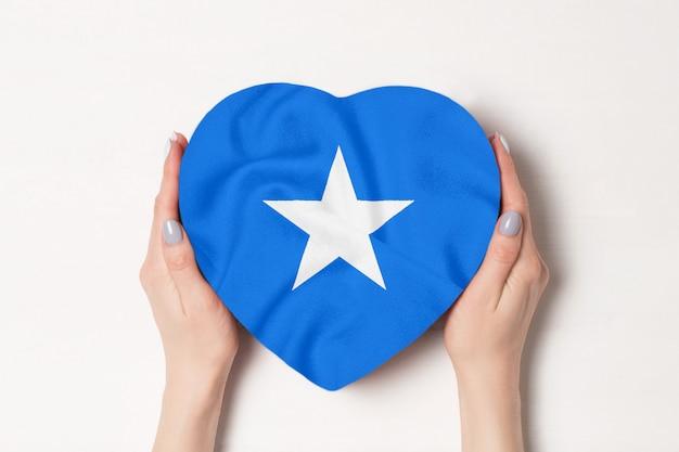 女性の手でハート型ボックスにソマリアの旗。白色の背景 Premium写真
